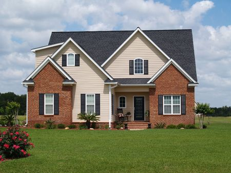 Two story residential home with both brick and board siding on the facade.     Imagens
