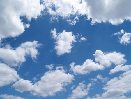 back ground: White puffy clouds in a blue sky      Stock Photo
