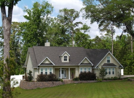 suburban neighborhood: One story residential home with board siding on the facade.    Stock Photo
