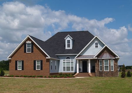 Two story residential home with brick, stone and board siding on the facade.