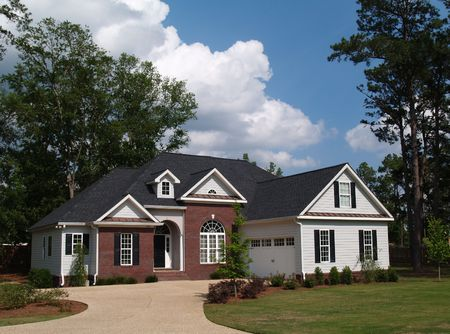 shutters: Two story residential home with brick and board siding on the facade.