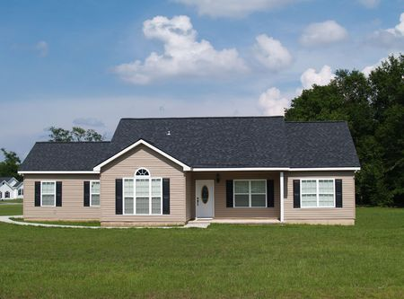 One story residential low income home with vinyl siding on the facade.        Archivio Fotografico
