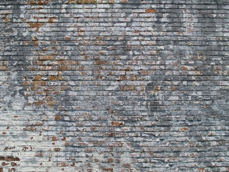 Old weathered and pealing white painted brick wall.