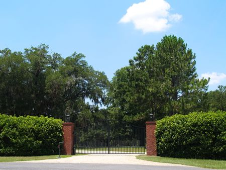 Black wrought iron security gate at the beginning of the lane of a country home.   photo