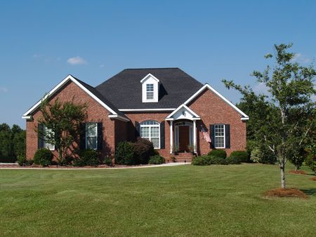 suburban neighborhood: One story new red brick residential home. Stock Photo