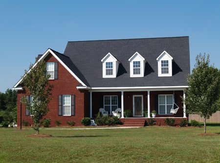 single story: Two story brick residential home with porch swing.