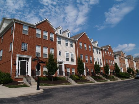 condos: A row of brick condos or townhouses beside a street.