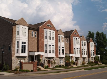 townhouses: A row of brick condos or townhouses with bay windows beside a street.