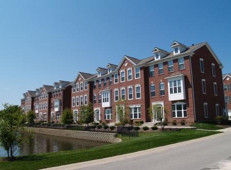 Una fila di ville o case a schiera di mattoni con vetrate accanto a una strada.