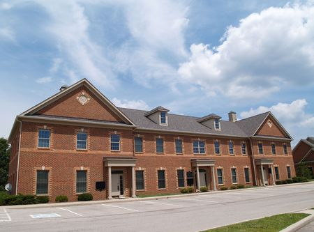Two story red brick office building with parking spaces.