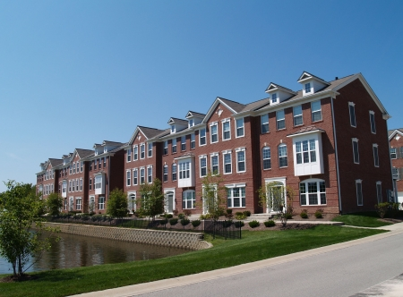 apartment building: A row of brick condos or townhouses with bay windows beside a street.