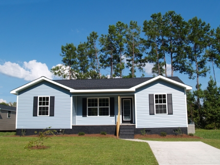 Powder blue low-income single-story home with porch.