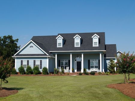 Blue two story board sided residential home with rocking chairs.