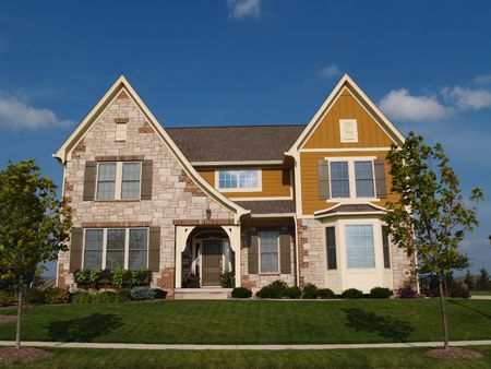 Two story stone, brick and board sided residential home with bay window. Standard-Bild