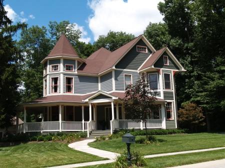 Nieuw verhaal twee Victoriaans woonhuis met vinyl of board siding op de gevel gestyled na een ouderwetse historisch huis met erkers, peperkoek en een torentje. Stockfoto