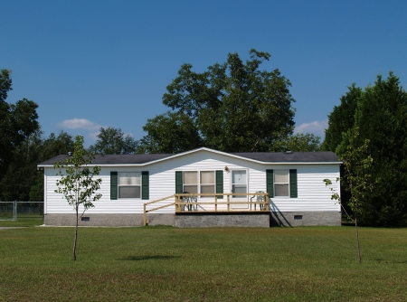 single story: White single-wide mobile residential low income home with vinyl siding on the facade. Stock Photo