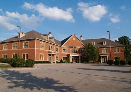 parking facilities: Dos pisos edificio de oficinas de ladrillo rojo con espacios de estacionamiento.