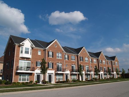 apartment: A row of brick condos or townhouses with bay windows beside a street.
