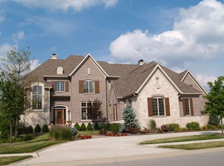 Two story brick and stone residential home with circle driveway.
