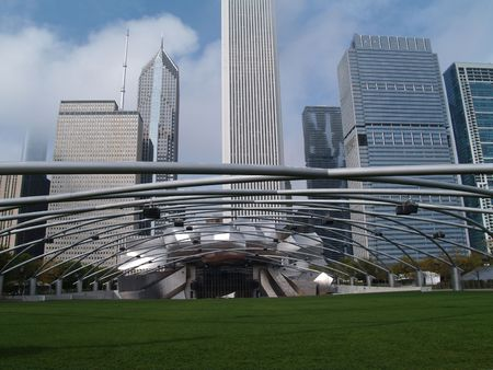 Grassy seating area of the Jay Pritzker Pavilion  showing the sound system supported on trellis style pipes in front of a Chicago skyline in Millennium Park.