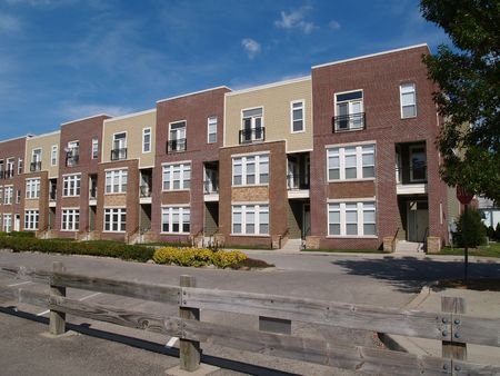 New townhouse or condo type homes made of different shades of brick and vinyl siding.