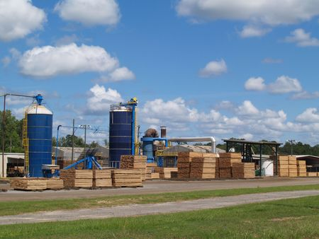 wood cut: Outside view of a south Georgia lumber yard with blue silos and stacks of fresh cut green lumber curing in the sunshine.