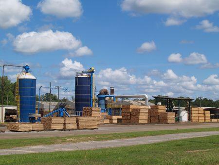 Vista esterna di un cantiere di legname Georgia del sud con silos di blu e pile di legname di verde taglio fresco essiccazione al sole.