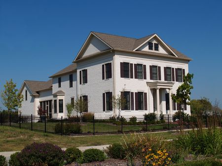 Two story new home built to look like an old historical home complete with the added on look, painted brick and a wrought  iron fence. Stock Photo - 5608285