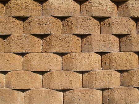 retaining: Rows of tan stone blocks that make up a retaining wall.