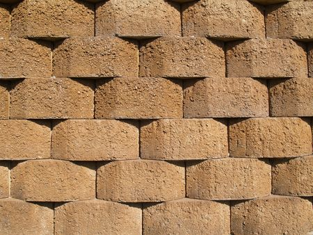 Rows of tan stone blocks that make up a retaining wall.