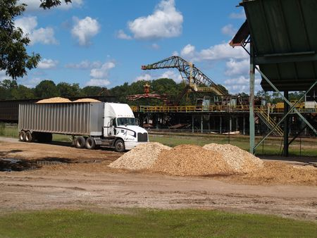 Pile of wood chips beside, filled semi truck alongside a lumberyard with logging crane working in the background.