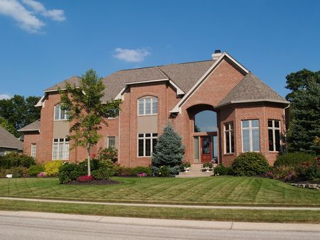 suburban home: Large two story new red brick residential home with a turret at the corner. Stock Photo