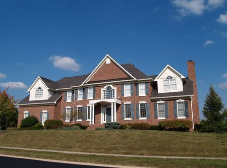 single story: Large two story brick residential home with blue shutters and dormers.