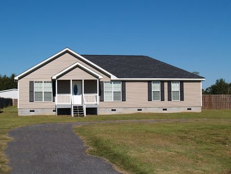 single story: Small low income manufactured home with a covered porch and vinyl siding.