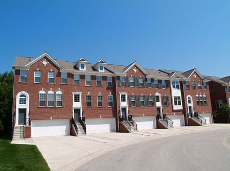 Red brick condos or town homes with the garage in the front. photo