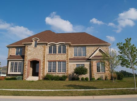 Two story contemporary stone residential home with arched windows. photo