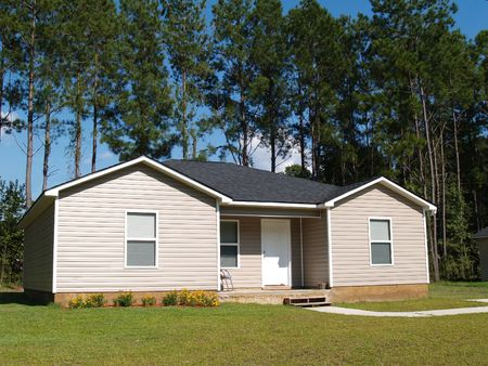 Small low income home with tan vinyl siding. Stock Photo - 6511115