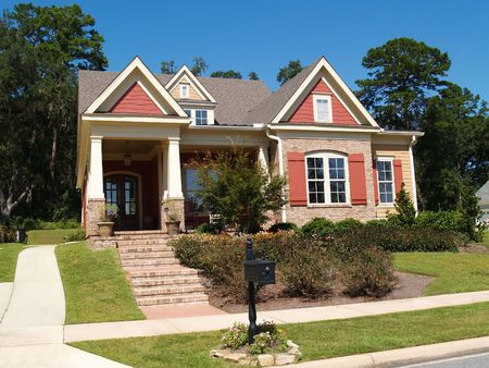 Beige brick home having peach and white trim with steps leading up to squares columns on the porch.