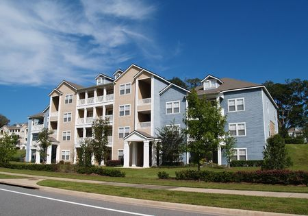 apartment buildings: Three story condos, apartments or townhomes with vinyl siding of blue and tan.   Stock Photo