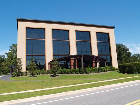 Three story office building with mostly glass front and an awning over the front walk.