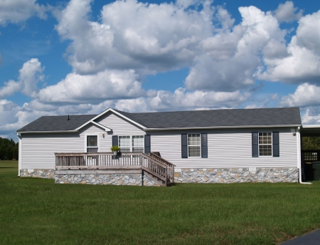 Gray trailer home with stone foundation or skirting and shutters in front of a beautiful sky. photo