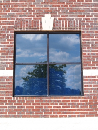 Four paned window on a red brick wall with special brickwork around it