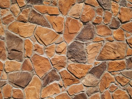 Multi-colored and multi-sized, orange and brown rock wall grunge texture background. photo