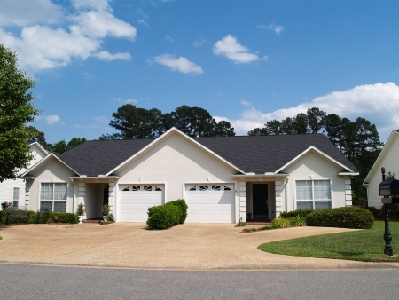 New low income small one story white vinyl duplex unit with garages in the front. Stockfoto