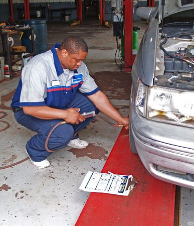 Auto mechanic inspecting a car's tire pressure in a service garage.
