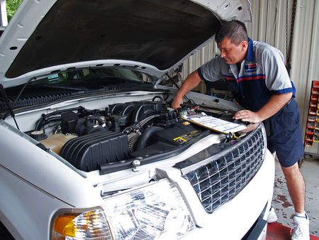 Auto mechanic performing a routine service inspection in a service garage. photo