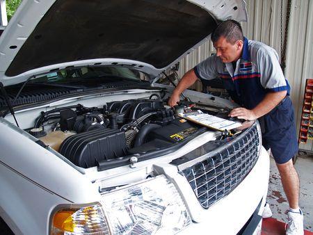 Kfz-Mechaniker, eine Routine-Service-Inspektionen in einer Service-Garage durchführen.  Standard-Bild - 7442810
