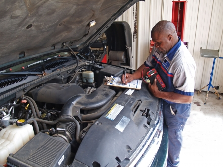 Auto mechanic performing a routine service inspection in a service garage