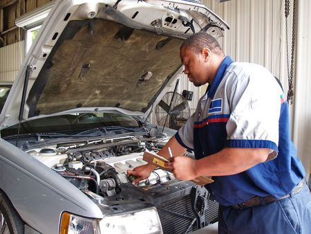radiator: Mechanic Performing a Routine Service Inspection