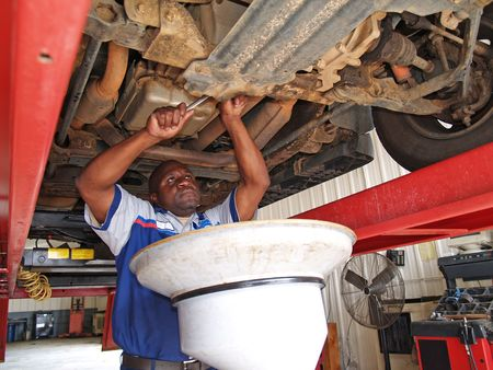 Auto mechanic performing an oil change with the car on a lift in a service station garage.